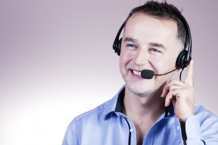 Businessman in blue shirt, a headset with a phone call  Stock Photo - 16661419