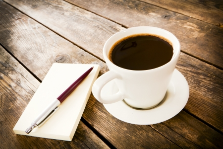 Notebook and coffee on the wooden table  photo
