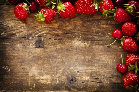 Strawberry and cherry on the old brown wooden background  photo