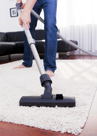 Young man is cleaning in the carpet