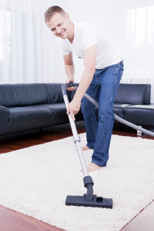 Young attractive man is cleaning vacuum on carpet