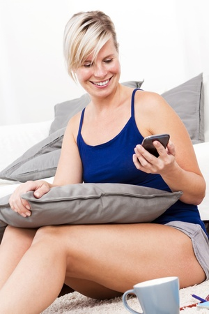 Blonde woman with phone in the living room  photo