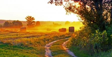 Sunset over the fields, and straw  Stock Photo
