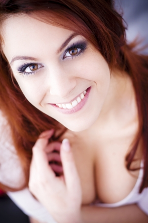 Beautiful red-haired girl smiles  photo