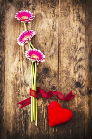 Gerbera and red heart on the wooden board  photo