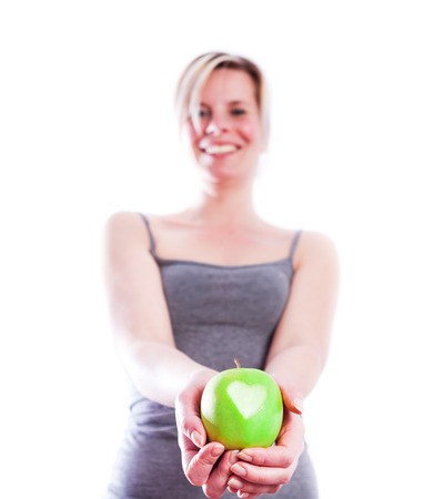 Attractive girl with apple in hand on heart symbol  photo