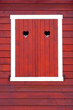 Stained wood window shutters closed, her heart symbol  photo