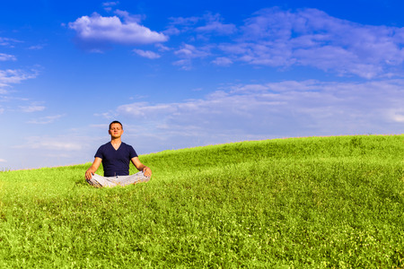 The peaceful scenery of a man meditating in the lotus position. Standard-Bild