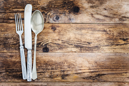 Old ornate wooden board with cutlery. Stock Photo