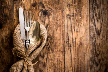 The old wooden table cutlery on the burlap.