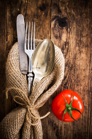 The old wooden table cutlery, and tomatoes.