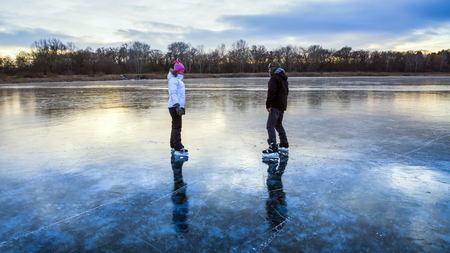 Young woman and man ice skating on the frozen lake in Hungary. The ice wonderfully reflected. photo
