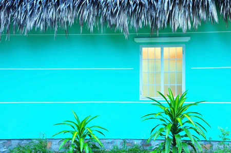 a blue green house in vietnam is opening the light and the orange light is comming out from the window