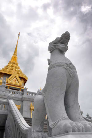 Singha and temple at Wat Trimit photo