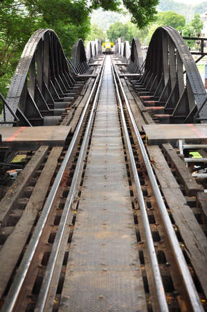 the train is coming from the end of railway crossing the river at Kwa River in thailand