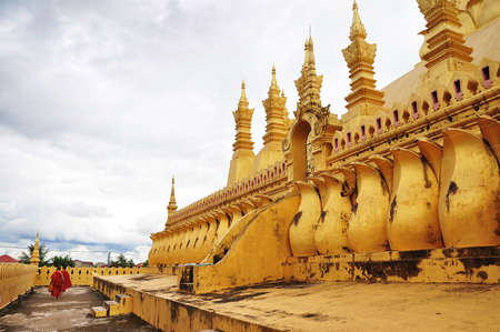 2 monks are walking beside the golden cheddi in Wat Thadlaung at vientien laos Stock Photo