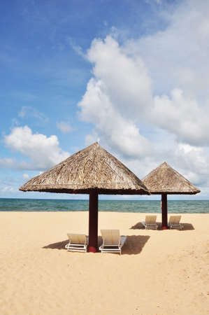 Cane umbrella and deck chairs on the sandy beach near the blue sea - Phu Quoc island in vietnam photo