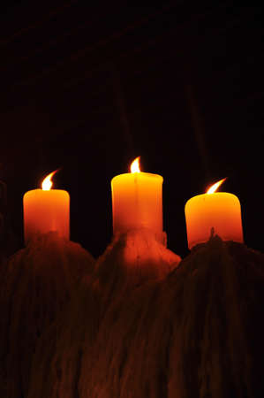 tripple: tripple candle showing candlelight in the dark Stock Photo
