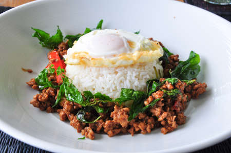 stir fried pork with basil and egg served with rice Stock Photo