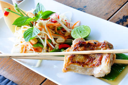fusion: Somtum - the spincy papaya salad in thai style served with grilled chicken Stock Photo