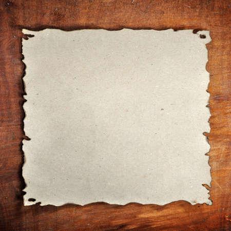 papel quemado: el papel quemado en el fondo de madera