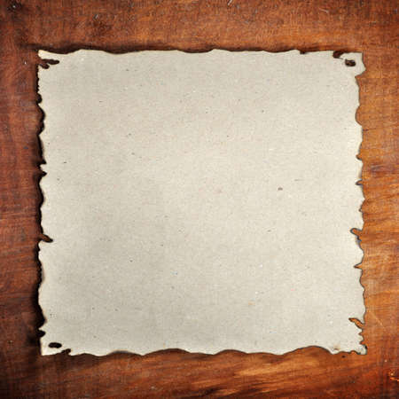 the burned paper on the wood background photo