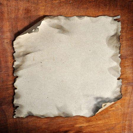 quemadura: el papel quemado en el fondo de madera para dise�os
