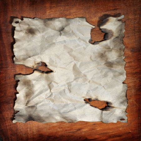 the burned paper was place on the wood backgound Stock Photo