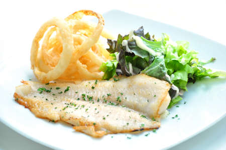 Seasoned fish steak fillet with onion rings Stock Photo