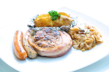 Grilled fillet wrapped with bacon served with sausages and baked potatoes photo