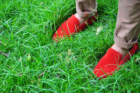 The red shoes contrast with the green grass photo
