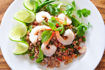 namtok: Thai spicy pork and shtimp salad served with fresh lime and cilantro Stock Photo
