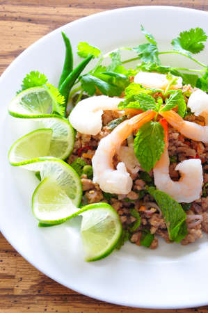 Thai spicy pork and shtimp salad served with fresh lime and cilantro Stock Photo