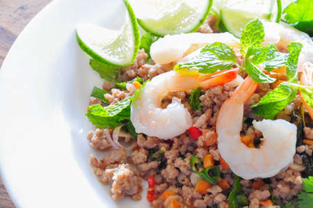 Thai spicy pork and shtimp salad served with fresh lime and cilantro Reklamní fotografie