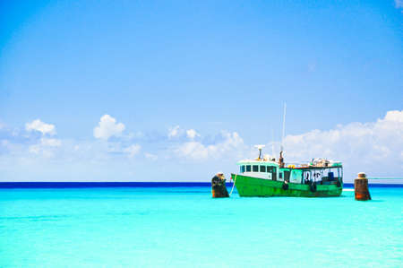 The fisherman boat floating on the clear ocean and blue sky Stock Photo