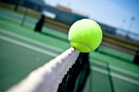 Close-up of a tennis ball clipping the net and falling to the other side.