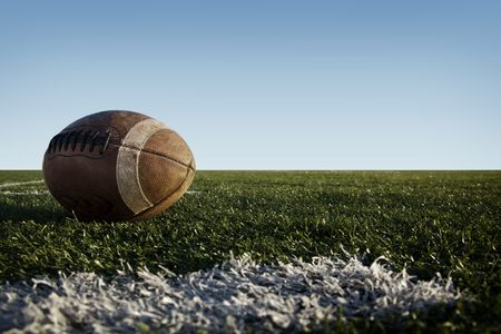 dirty football: American football laying on a field.