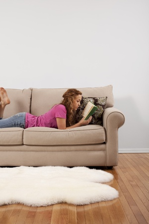woman on couch: A young woman reads a book comfortably on her couch.