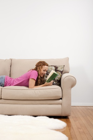 A woman smiles and enjoys a book at her home. Stock Photo - 9767041