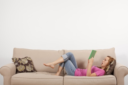 A young woman is shocked at what she reads in a book. Stock Photo - 9767040