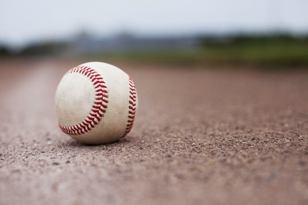 spring training: A ball lying on the infield of a baseball field. Shallow depth of field.  Stock Photo