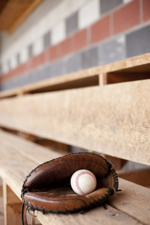 Baseball and glove sitting in a dugout on a bench.