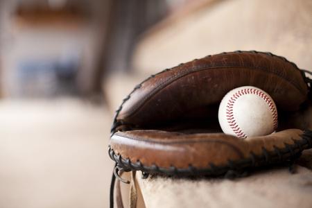 baseball dugout: B�isbol y guante sentado en un dugout en un banco.  Foto de archivo