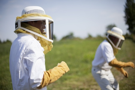 Two bee keepers dressed in protective suits get ready to check a bee hive in the country.