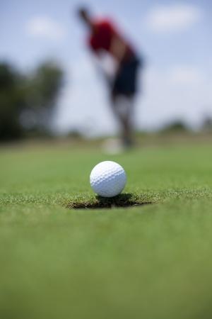 남자는 녹색에 골프 공을 퍼팅.