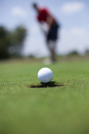 putting green: A man putts a golf ball on the green.