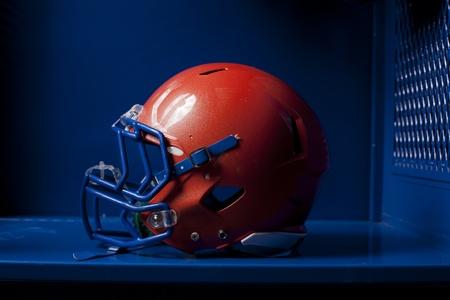 locker room: An american football helmet sits in an empty locker. Dramatic lighting.