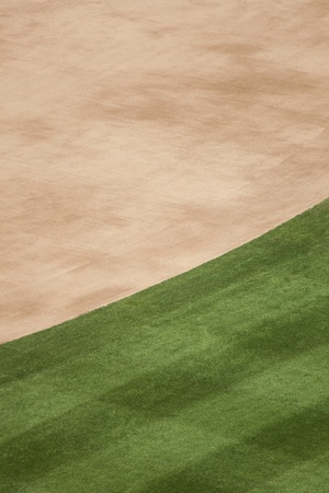 infield dirt and outfield grass background at a baseball stadium.