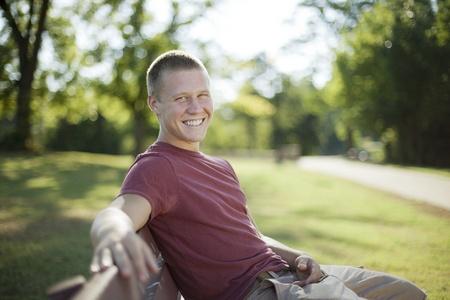 hombres jovenes: Apuesto joven sentada en un banquillo sonriendo. Franco.