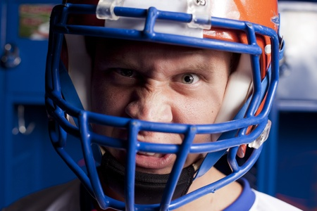 Close up of an american football player with helmet in locker room.